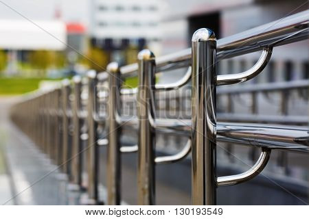 Chromium metal fence with handrail. Chrome-plated metal railings. Shallow depth of field. Selective focus.