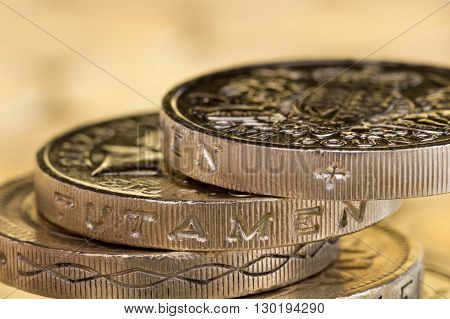 Close up of British money pound coins precariously balanced.