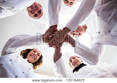Portrait of chefs team putting hands together and cheering in a commercial kitchen