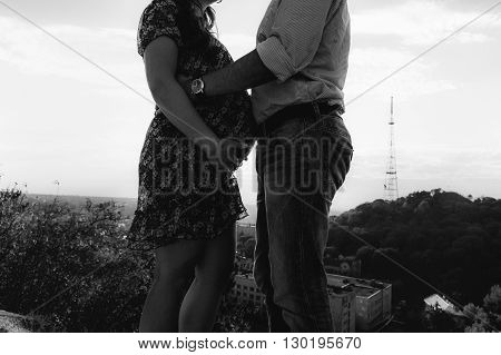 Handsome Man & Pregnant Woman Posing At Sunrise On Cliff, Closeup B&w