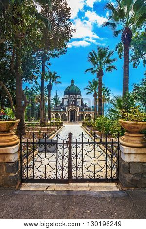 Roman Catholic Church of the Beatitudes.  Stone path leading to the monastery. Openwork metal gate closes the entrance to the basilica