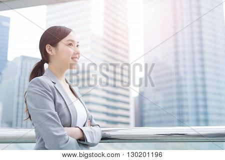 business woman smiles and looks with office background asian beauty shot in Hong Kong