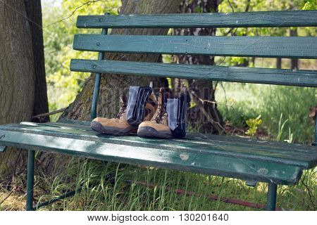 Hiking shoes with socks on green bench