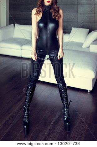 Sexy dominatrix in latex catsuit and handcuffs posing in luxury flat indoors bdsm