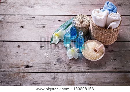 Spa or wellness setting in blue yellow and white colors. Bottles wih essential aroma oil towels sea salt on aged wooden background. Selective focus. Place for text.