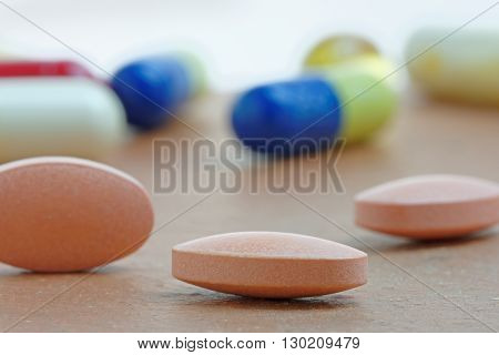 Close up of statin tablet or generic pill with out of focus tablets in background
