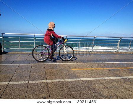 Beirut, Lebanon - January 09, 2016: one girl's biking  walking via Beirut's famous seaside promenade, Lebanon