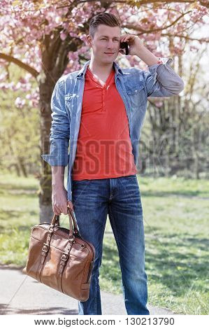young man in park walking and talking on phone