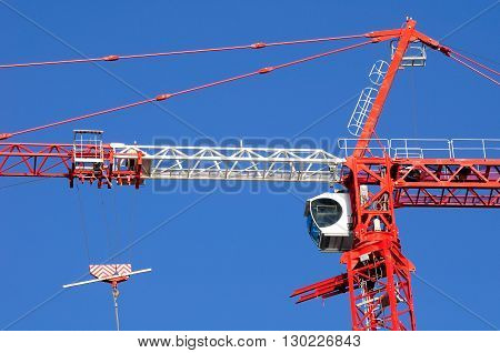 Assembled construction crane against blue cloudless sky.