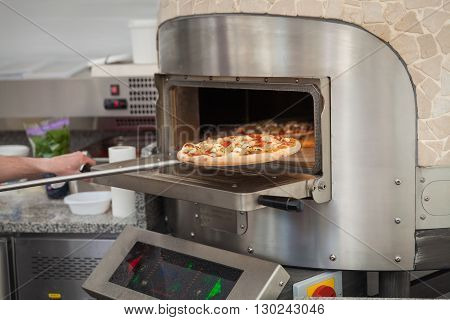 cook pulls lave baked pizzas from a stone oven