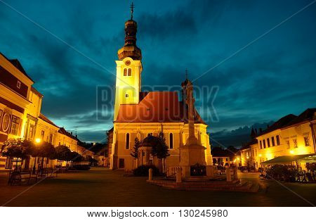 Night view of Jurisics square in Koszeg with Maria statue and St. Imre church Hungary.