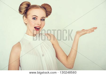 Close-up portrait of surprised beautiful girl with funny hairstyle open hand and open-mouthed.