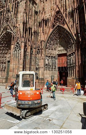STRASBOURG FRANCe - MAY 04 2016: Red Kubota tractor arranging granite pavement sones in from of Strasbourg Cathedral