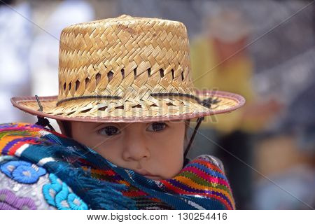 CHICHICASTENANGO GUSTEMALA APRIL 29 2016: Portrait of a Mayan baby carried on the back of his mother. The Mayan people still make up a majority of the population in Guatemala,