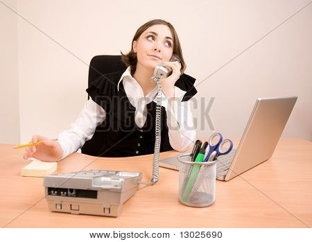Young businesswoman sitting in the chair and talking by phone poster