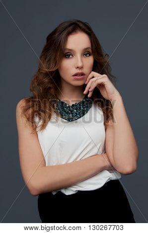 Sensual young beautiful woman with languishing look wearing white blouse and beaded green necklace