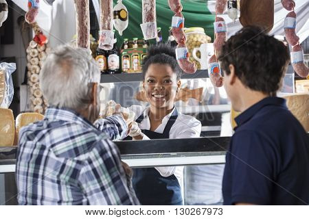 Saleswoman Selling Cheese To Male Customers At Shop