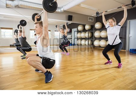 Determined Men And Women Lifting Dumbbells On Hardwood Floor