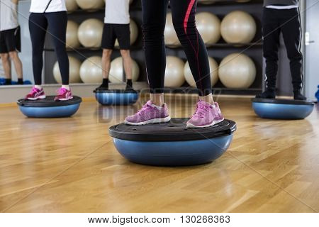 Low Section Of Friends Standing On Bosu Ball In Gym