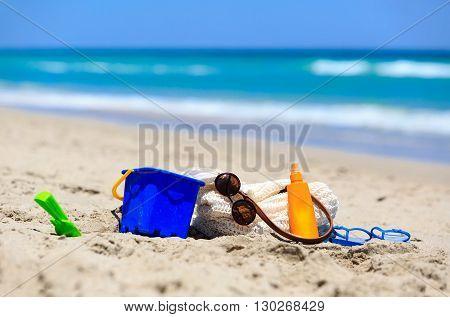 vacation concept - beach bag, suncream, kids toys on the beach