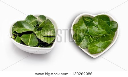 Bergamot leaves  in a heart shaped bowl, isolated on white