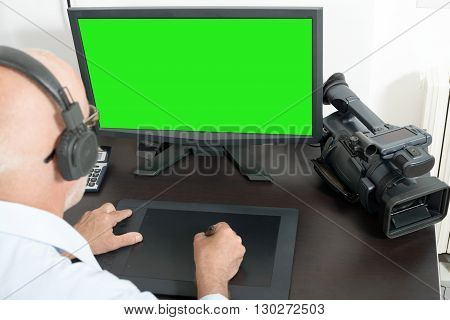 a mature man video editor in his studio