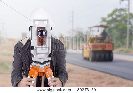 Engineer Working With Survey Equipment Theodolite With Road Under Construction
