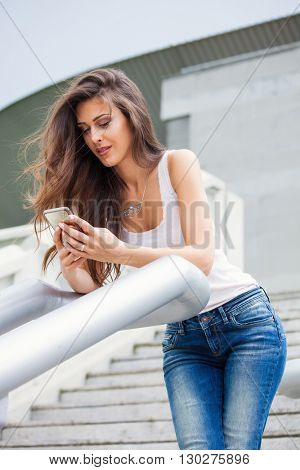 young urban girl with smartphone in blue jeans and white sleeves t-shirt lean on handrail on stairs summer day in city