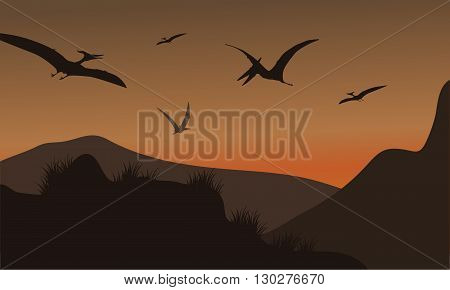 Silhouette of pterodactyl flying at afternoon with brown backgrounds
