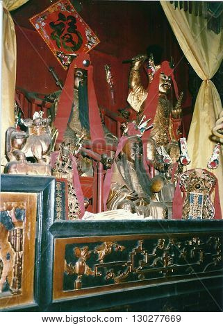 MACAU - CIRCA 1987: Sacred images stand on an altar inside the Kun Iam Buddhist Temple in Macau.