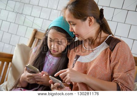 Asian mother advices her daughter about using smartphone on sofa at home