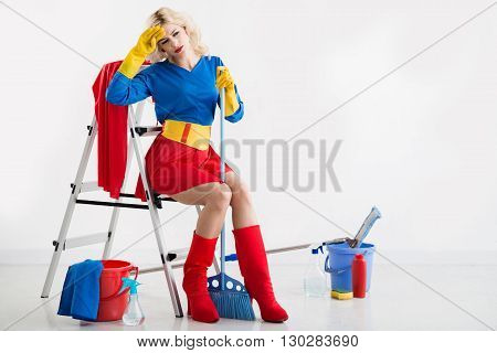 Tired pretty young  housewife in superwoman costume