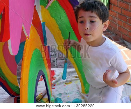 Young boy painting an art project outdoors.