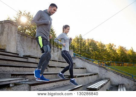 fitness, sport, people and lifestyle concept - couple running downstairs on stadium