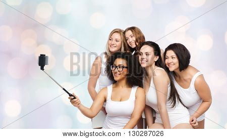 technology, friendship, body positive and people concept - group of happy women in white underwear taking picture with smartphoone on selfie stick over holidays lights background