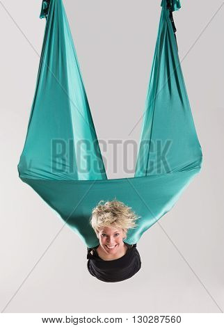 Smiling Woman Doing Aerial Yoga In Mid Air
