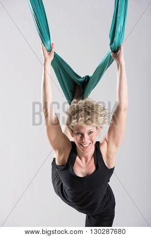 Happy Woman Using Tarp For Aerial Yoga Workout