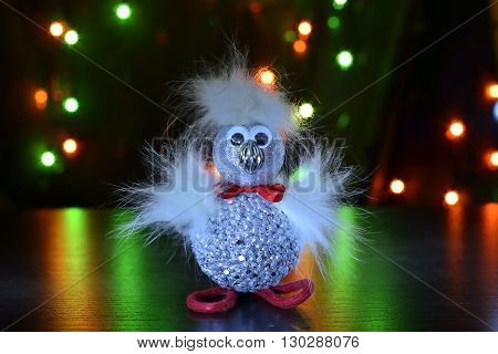 fluffy phoenix toy over dark bokeh background