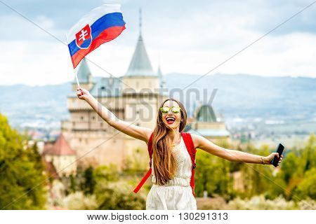Young female tourist having fun traveling with slovak flag at Bojnice castle in Slovakia. Promoting tourism in Slovakia