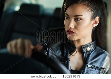 Portrait of young attractive unsmiling woman driving
