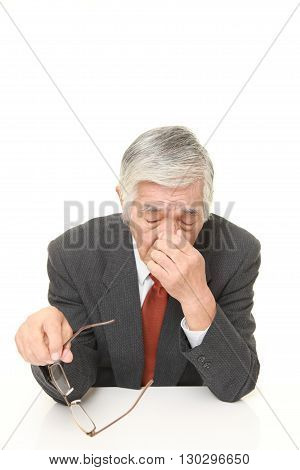 portrait of senior Japanese businessman suffers from Asthenopia on white background