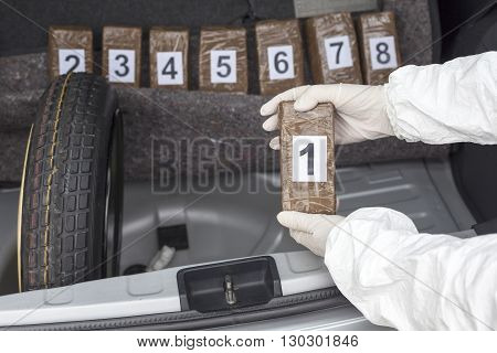 Drug trafficking. Drug bundles smuggled in a car trunk.
