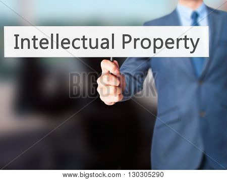 Intellectual Property - Businessman Hand Holding Sign