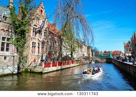 Bruges, Belgium - April 10, 2016: Scenic cityscape with medieval houses, boat with tourists and canal in Bruges, Belgium