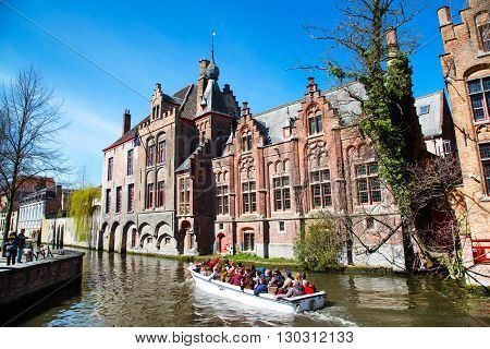 Bruges, Belgium - April 10, 2016: Scenic cityscape with medieval houses boat with tourists and canal in Bruges, Belgium