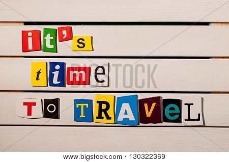 Time to Travel - written with color magazine letter clippings on wooden board.