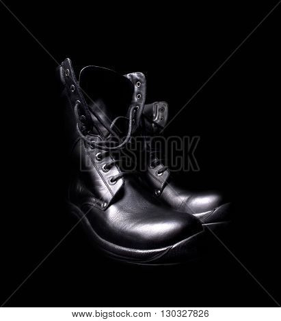side view of a pair of shiny black leather boots with untied shoe laces on black background