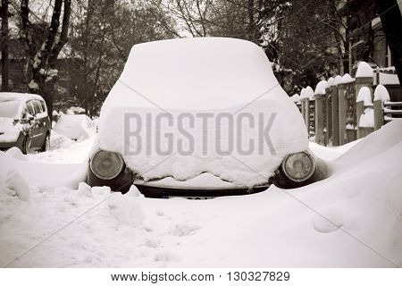 Horizontal front view picture of a car covered in snow on a street with round headlights showing