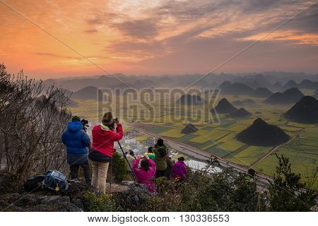 YUNNAN,CHINA-FEBRUARY 26,2016 :Tourist taking a picture for sunrise on the rock view from Luoping,Yunnan,China