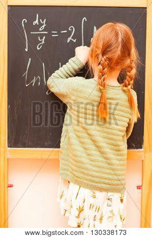 Back to school concept. Little girl writing formulas on blackboard